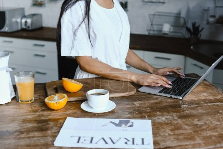 Photo for Cropped image of mixed race girl in white robe using laptop in morning in kitchen - Royalty Free Image