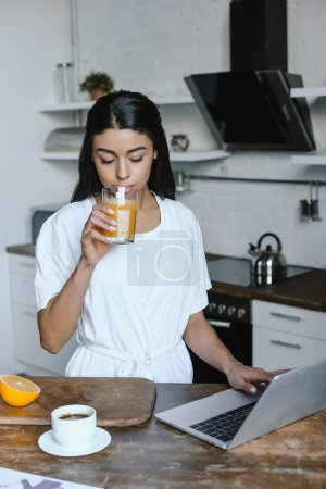 beautiful mixed race girl in white robe drinking juice in morning in kitchen