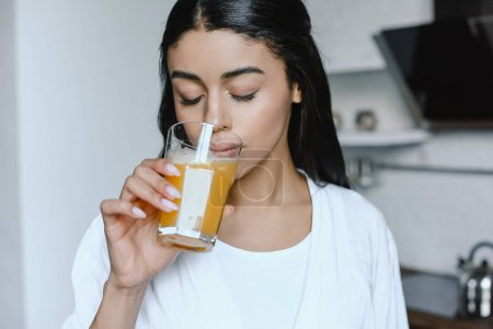 Photo for Beautiful mixed race girl in white robe drinking fresh orange juice in morning in kitchen with closed eyes - Royalty Free Image