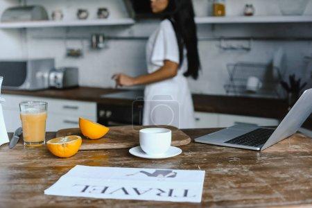 Photo pour Fille de race mixte en robe blanche le matin dans la cuisine, tasse de café et journal de voyage sur table - image libre de droit
