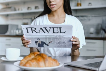 Photo for Cropped image of mixed race girl in white robe reading travel newspaper in morning in kitchen - Royalty Free Image