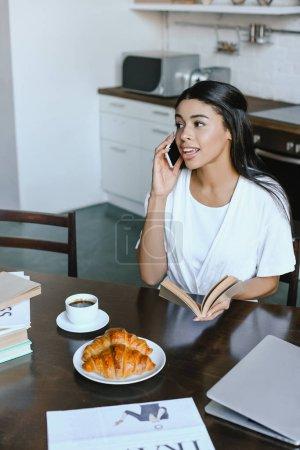 Photo pour Sourire attrayant mélangés course fille en robe blanche parlant par smartphone matin dans la cuisine et la tenue de livre - image libre de droit