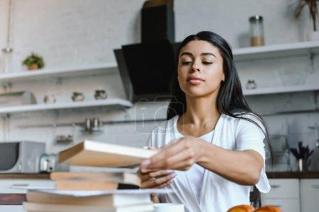 Photo pour Niveau de la surface de fille belle métisse dans livre de prise robe blanche dans la matinée en cuisine - image libre de droit