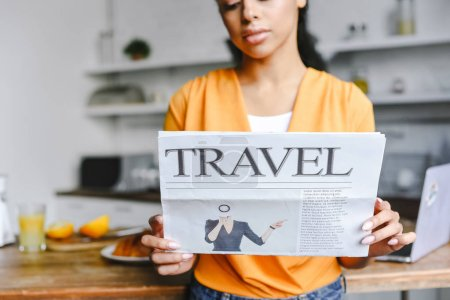 Photo for Selective focus of beautiful mixed race girl in orange shirt holding travel newspaper in kitchen - Royalty Free Image