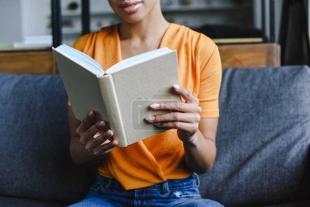 Photo pour Image recadrée de fille de race mixte en chemise orange livre de lecture dans le salon - image libre de droit