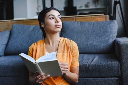 Photo pour Belle fille de race mixte en chemise orange tenant livre dans le salon et détournant les yeux - image libre de droit