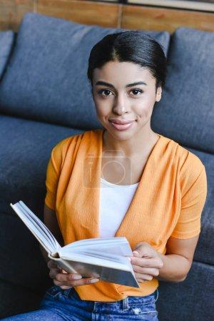 Photo pour Belle fille mixte en chemise orange tenant livre dans le salon et regardant la caméra - image libre de droit