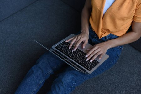 Photo for Cropped image of mixed race girl in orange shirt using laptop in living room - Royalty Free Image