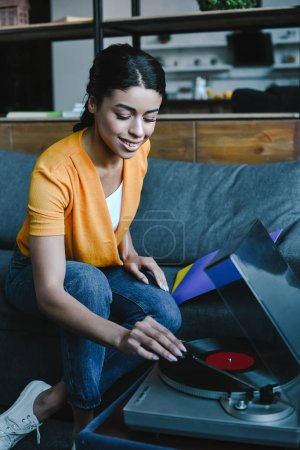 smiling beautiful mixed race girl in orange shirt turning on gramophone with retro vinyl at home