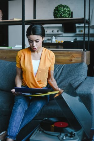 Photo pour Attractive mixed race girl in orange shirt choosing vinyl on sofa in living room - image libre de droit