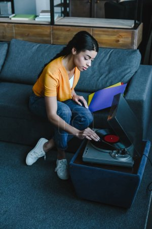 high angle view of beautiful mixed race girl in orange shirt turning on gramophone with retro vinyl at home
