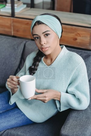 Photo for Attractive mixed race girl in turquoise sweater and headband sitting on sofa and holding cup of tea in living room - Royalty Free Image