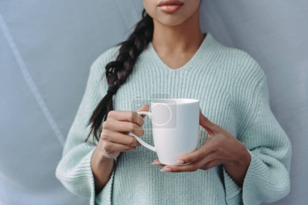 Photo for Cropped image of mixed race girl in turquoise sweater holding cup of tea at home - Royalty Free Image