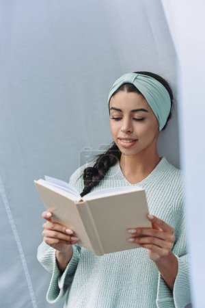 beautiful mixed race girl in turquoise sweater and headband reading book at home