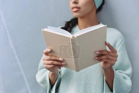 Photo for Cropped image of mixed race girl in turquoise sweater and headband holding book at home - Royalty Free Image