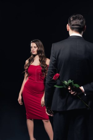 man hiding rose behind back with woman in red dress on background isolated on black