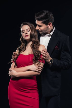 Photo for Man embracing woman in red dress isolated on black - Royalty Free Image