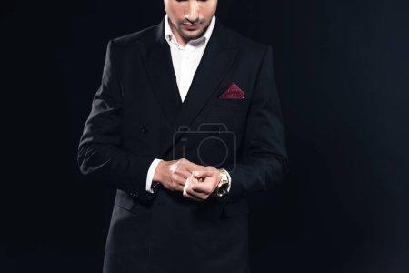 Photo pour Vue recadrée de l'homme en costume mettant sur montre isolée sur fond noir - image libre de droit