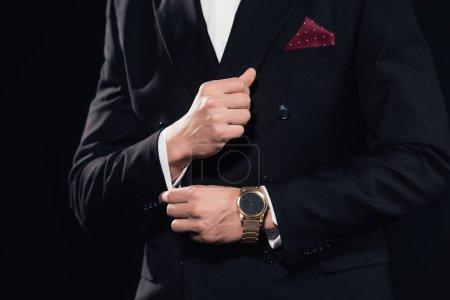 Photo pour Vue recadrée de l'homme en ajustant les boutons de manchettes sur le costume isolée sur fond noir - image libre de droit