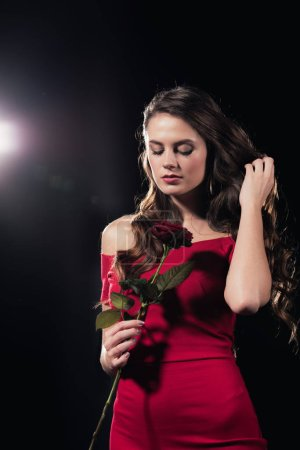woman in red dress with eyes closed holding rose on black background