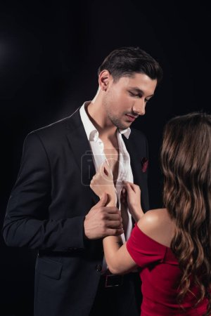 woman in red dress undressing handsome man isolated on black