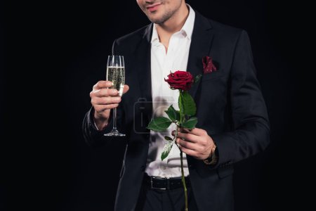 cropped view of man holding glass of champagne and red rose isolated on black