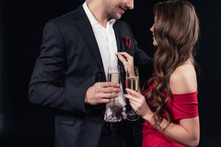 smiling romantic couple holding champagne glasses isolated on black