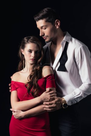 beautiful young romantic couple in formal wear hugging isolated on black