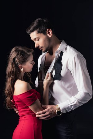 woman in red dress undressing man shirt isolated on black