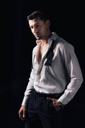 Photo pour Bel homme en chemise blanche et la main dans la poche en regardant la caméra tout en posant isolé sur noir - image libre de droit