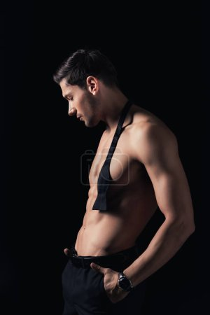 handsome shirtless man with hands in pockets posing isolated on black