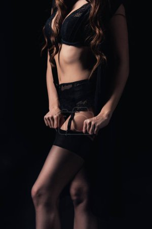 partial view of woman in lingerie putting on stocking isolated on black