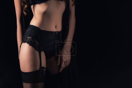 midsection of woman in lingerie isolated on black