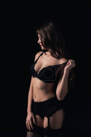sexy woman looking away and posing in lingerie isolated on black
