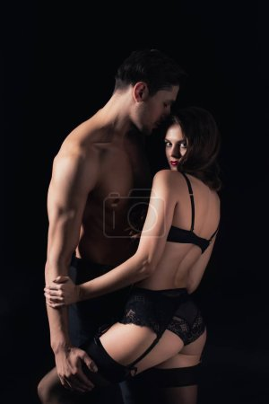 Photo for Woman in lingerie looking at camera and posing with shirtless man isolated on black - Royalty Free Image