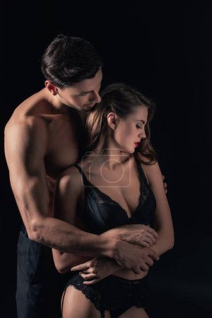Photo pour Sexy couple dévêtu étreindre isolés sur noir - image libre de droit