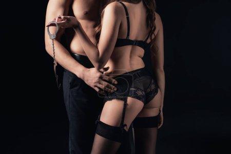 abgeschnittene Ansicht von hemdlosen Mann umarmt Frau in Dessous mit Handschellen isoliert auf schwarz