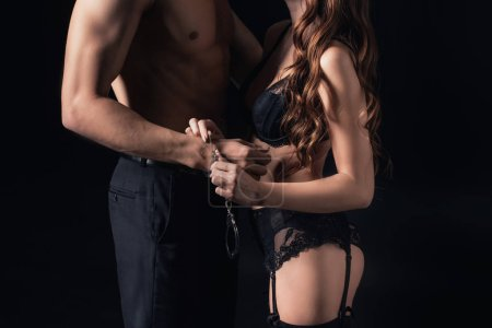 cropped view of woman in lingerie putting handcuffs on shirtless man isolated on black