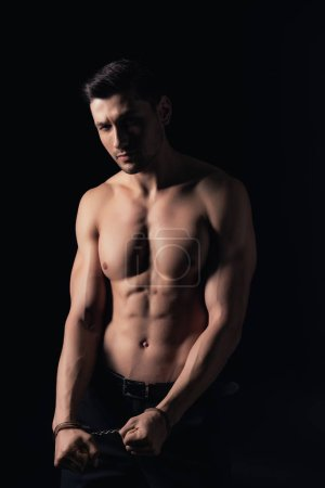 shirtless man in handcuffs looking at camera isolated on black