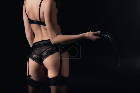 cropped view of woman in lingerie holding leather flogging whip isolated on black