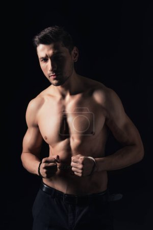 handsome shirtless man in handcuffs looking at camera isolated on black