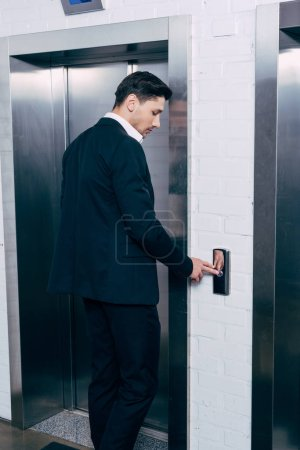 man in black suit pressing elevator button