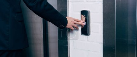 cropped view of man pressing elevator button