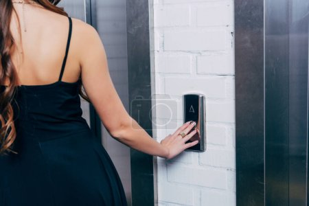 back view of woman in black dress pressing elevator button