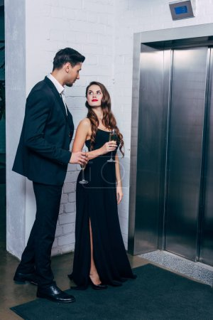 beautiful couple in formal wear holding champagne glasses and waiting for elevator