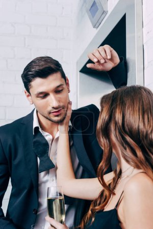 woman holding champagne glass and touching face of man while waiting for elevator