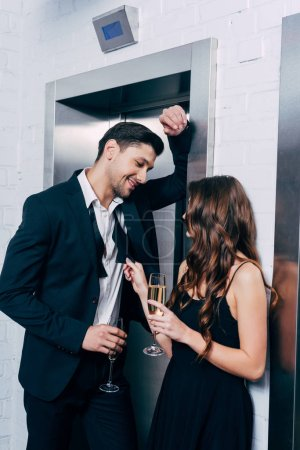 couple in formal wear holding champagne glasses, talking and waiting for elevator