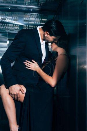 Photo pour Couple séduisant baisers et câlins dans l'ascenseur - image libre de droit
