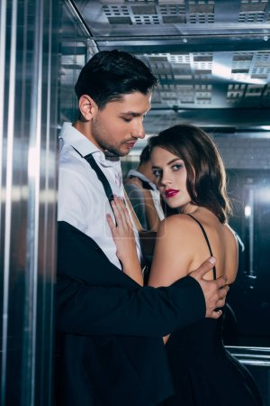 beautiful woman looking at camera man and embracing handsome man in elevator