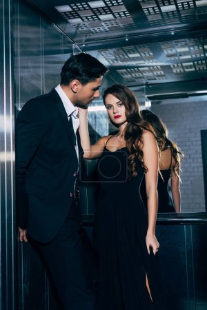 beautiful woman looking at camera man and touching man face in elevator